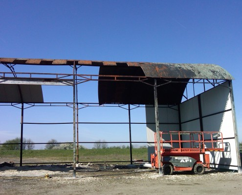 Fire-damaged Dutch Barn strip & re-sheet with new curved metal roof sheeting